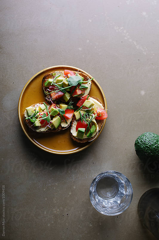 Avocado,tomato and samphire toasts on a plate.Avocado toast by Darren Muir for Stocksy United