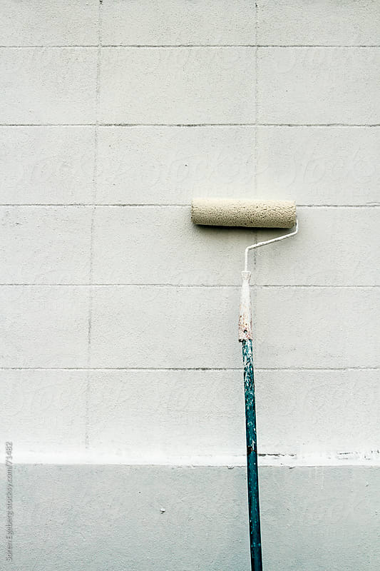 White paint roller with bue shaft leaning against white wall by Soren Egeberg for Stocksy United