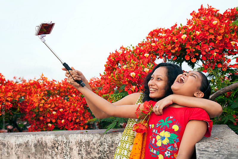Young woman and a teenager taking selfie together by PARTHA PAL for Stocksy United