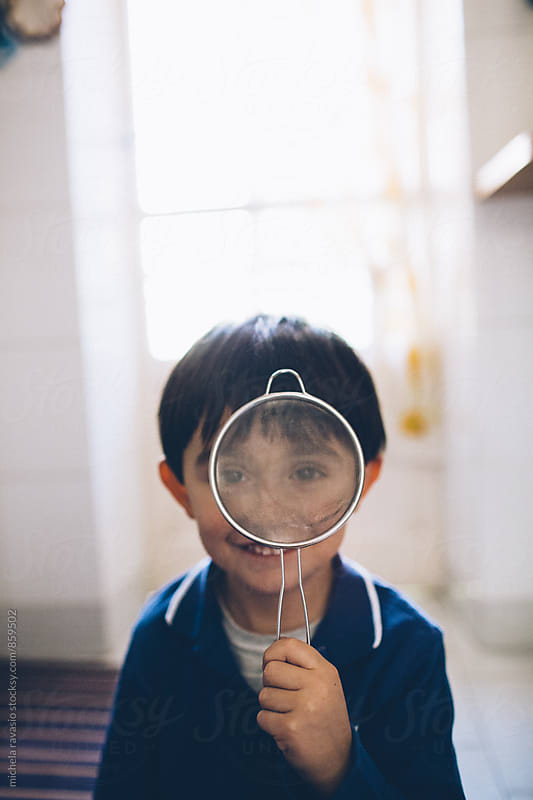 Smiling child playing looking through a colander by michela ravasio for Stocksy United