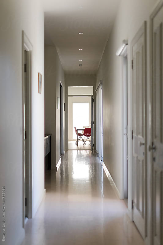 Looking down a hallway at kitchen chairs by Rowena Naylor for Stocksy United