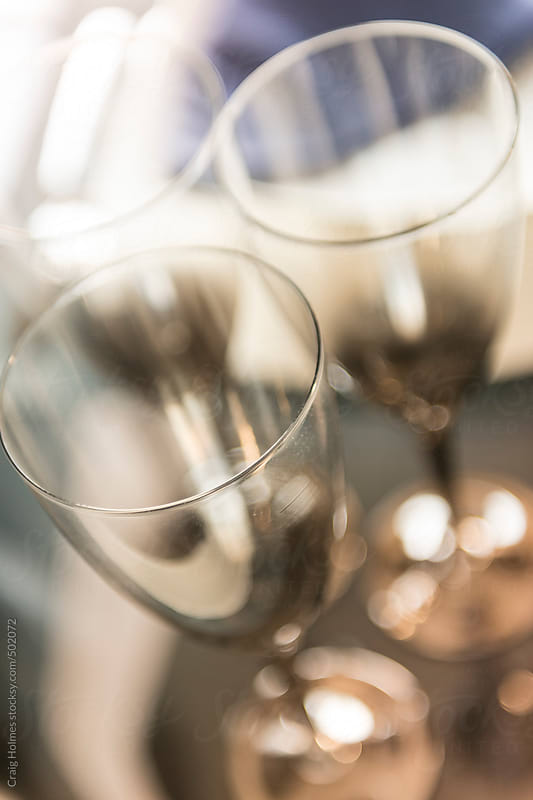 Wine glasses on a laid table by Craig Holmes for Stocksy United