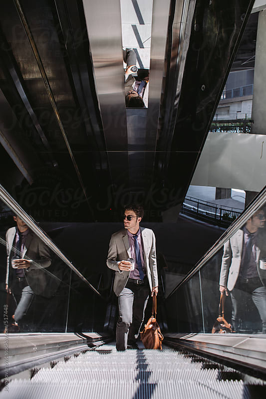 Stylish young man on an escalator at the airport by Jovo Jovanovic for Stocksy United