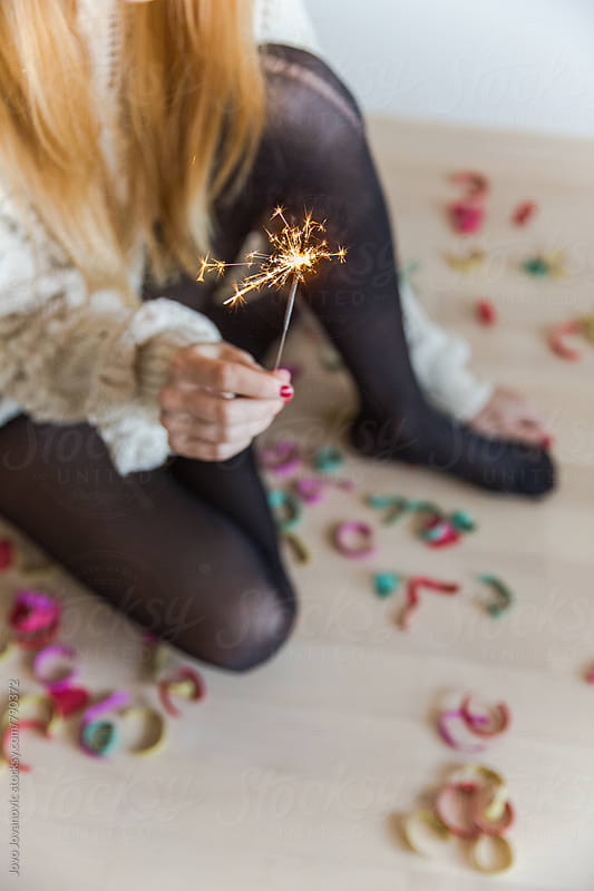 From above - woman holding a sparkler at home with confetti on the floor by Jovo Jovanovic for Stocksy United