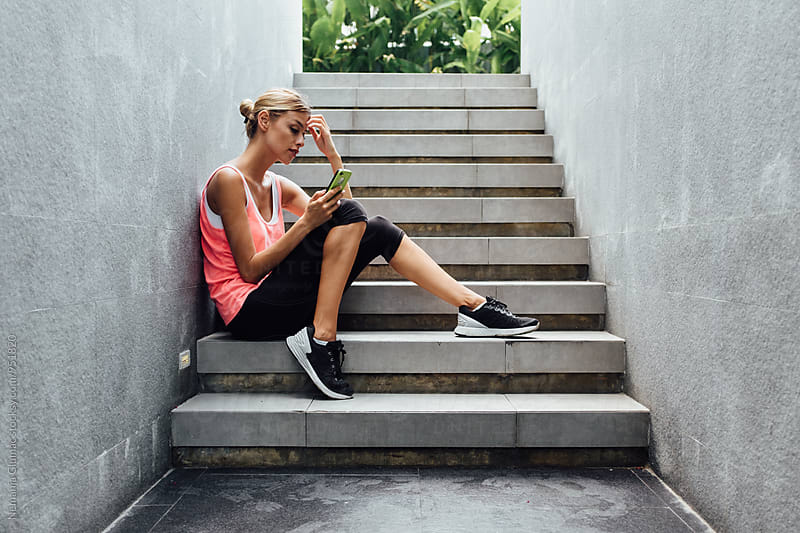 Pretty Fitness Woman Using Her Phone After Workout by Nemanja Glumac for Stocksy United
