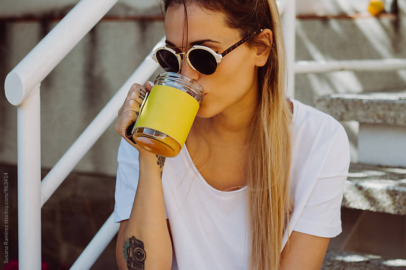 Portrait of young woman with sunglasses and cup by Susana Ramírez for Stocksy United