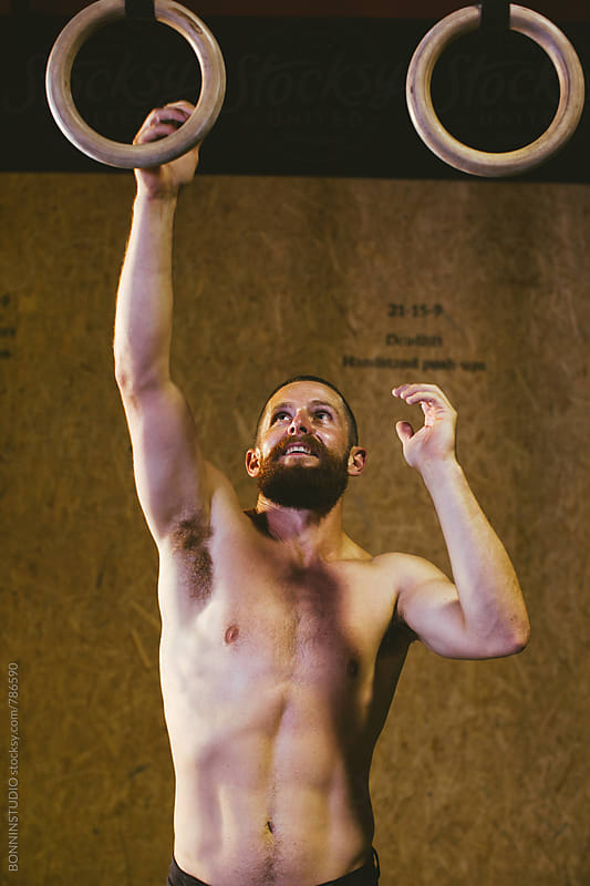 Man training with rings in a gym box. by BONNINSTUDIO for Stocksy United