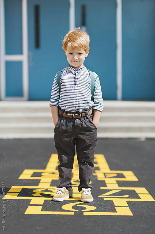 A boy standing on a playground with a mischievous smile and hands in his pockets by Ania Boniecka for Stocksy United