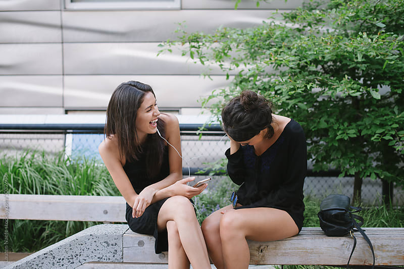 Friends sharing headphones and laughing by Lauren Naefe for Stocksy United