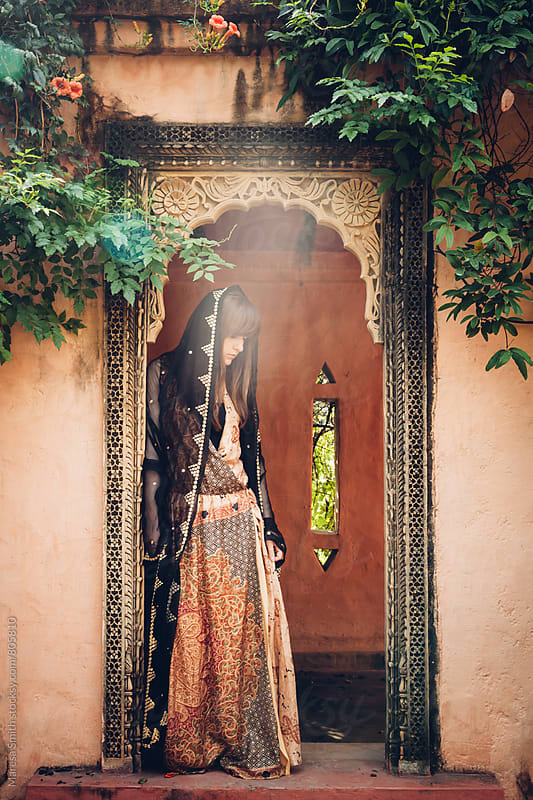A young women standing in an ornate doorway wearing a patterned maxi dress and sari shawl by Maresa Smith for Stocksy United