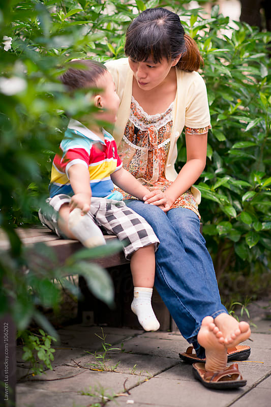 Kid and mother small talking in garden corner by Lawren Lu for Stocksy United