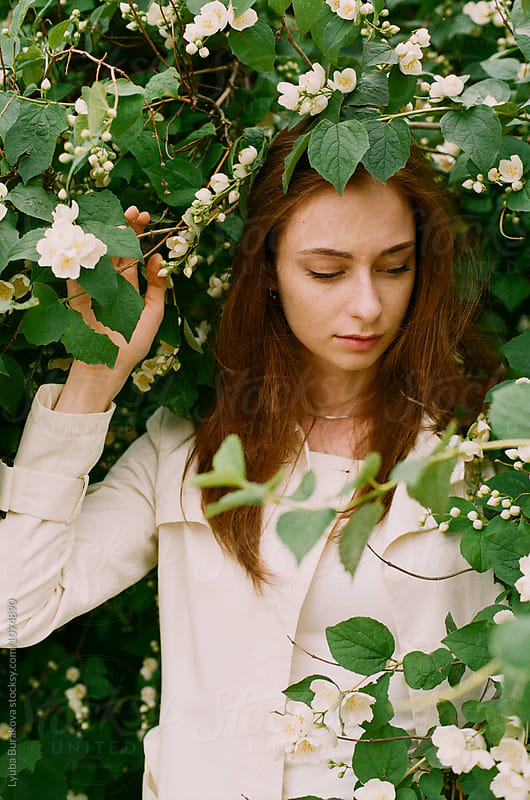 Young woman among jasmine by Liubov Burakova for Stocksy United