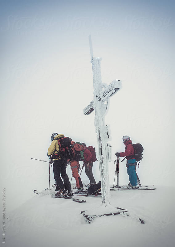 group of young freeskier on top of a summit with an iced summit cross by Leander Nardin for Stocksy United