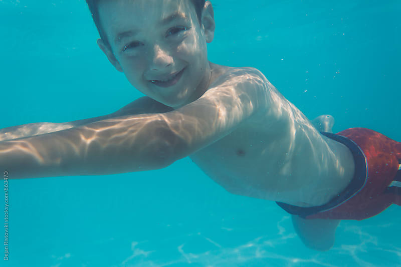 Boy smiling underwater. by Dejan Ristovski for Stocksy United