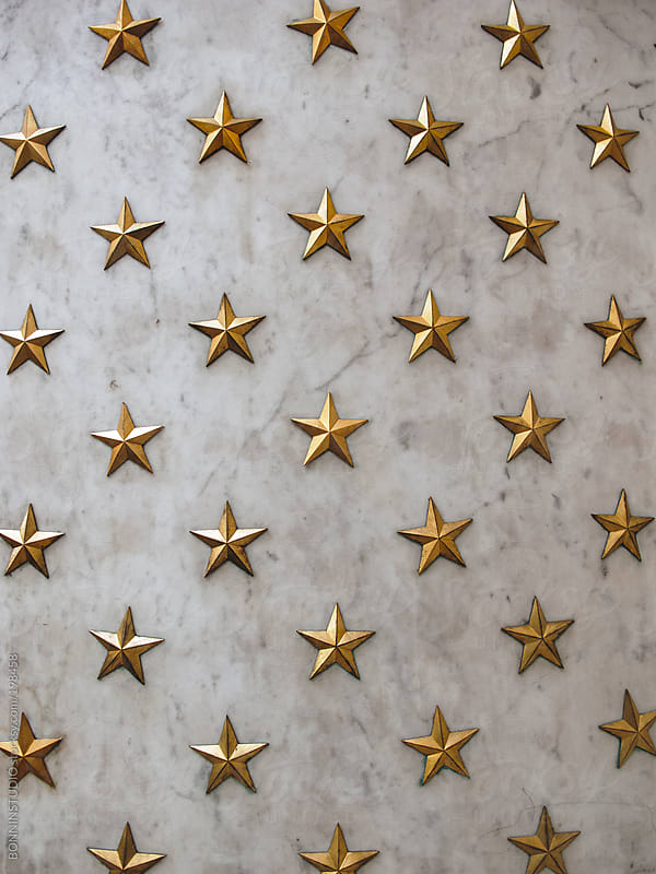Gold stars background on marble wall. by BONNINSTUDIO for Stocksy United