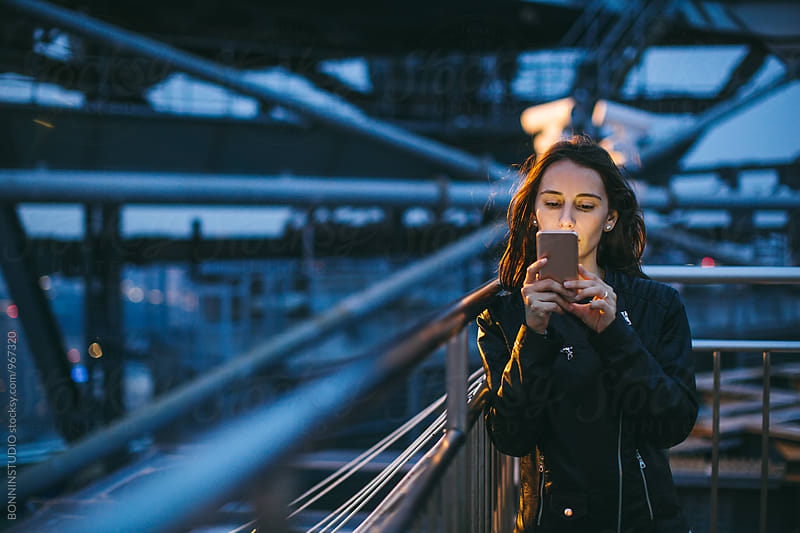 Young woman using her phone from rooftop at night. by BONNINSTUDIO for Stocksy United