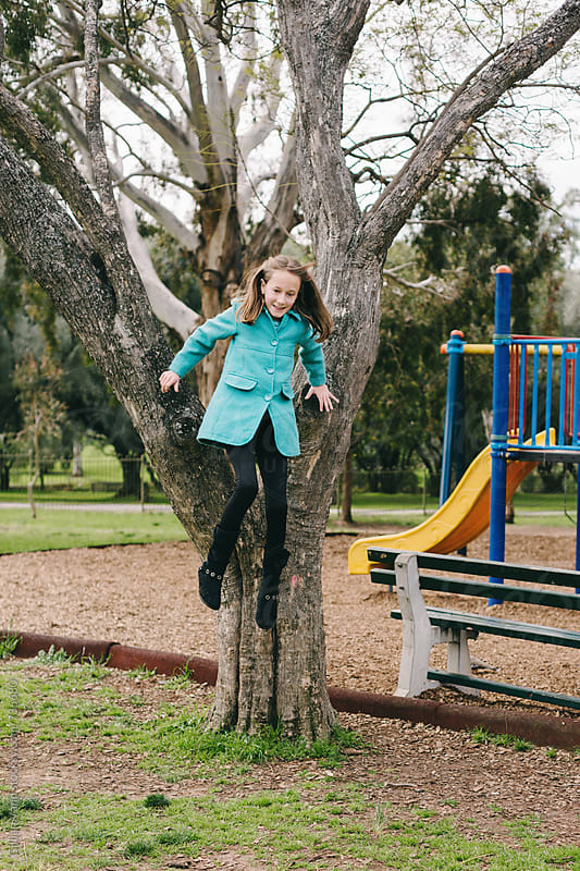 girl jumping from a tree at the park by Gillian Vann for Stocksy United