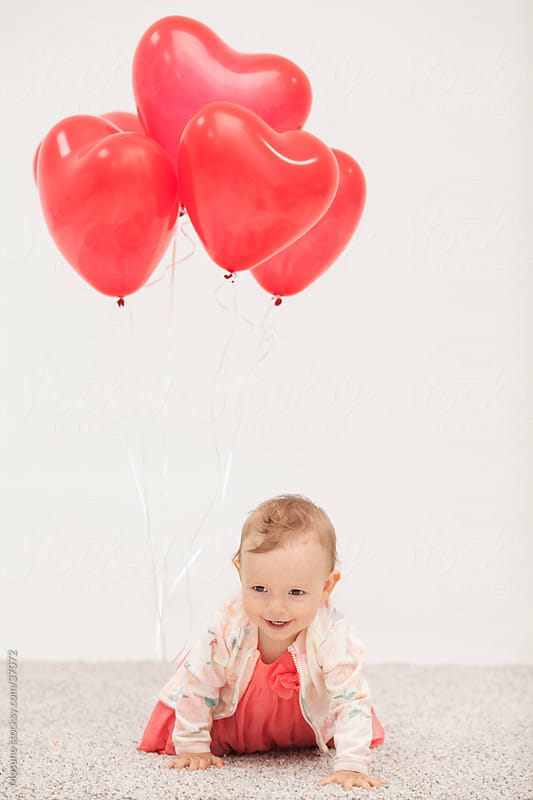 Cute little baby girl playing with heart shaped balloons and laughing at home. by Mosuno for Stocksy United