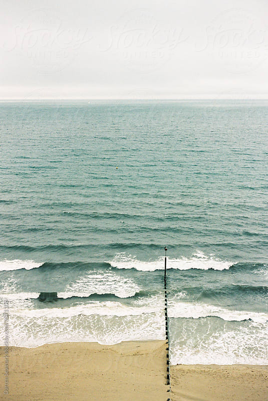 Beach scene with stormy sea and an overcast sky by Darren Seamark for Stocksy United