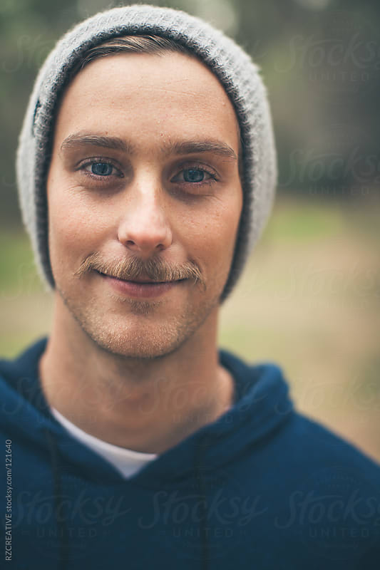 Portrait of young man wearing a grey beanie and blue hooded sweatshirt. by RZ CREATIVE for Stocksy United
