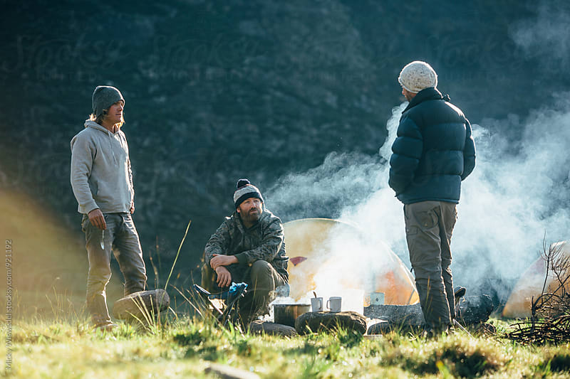 hikers around a campfire in a mountain camp by Micky Wiswedel for Stocksy United