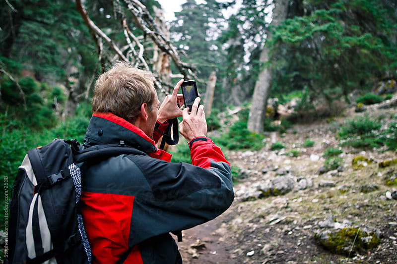 Hiker Using Camera Phone Outdoors by Stephen Morris for Stocksy United