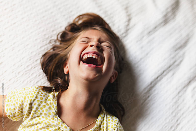 Little girl laughing uncontrollably by Amanda Worrall for Stocksy United