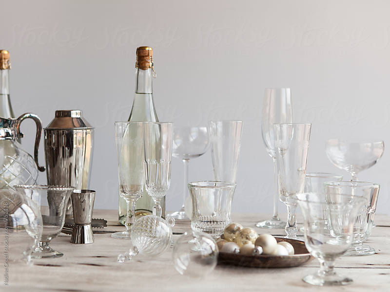 Barware, glasses, cocktail shaker, champagne bottles, tot measure and christmas baubles on table top by Nadine Greeff for Stocksy United