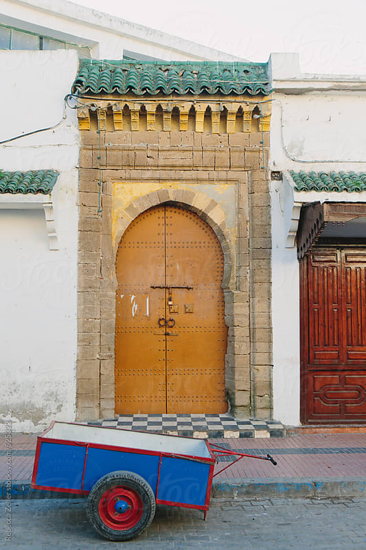 a cart outside a traditional door in the old town of essaouira, morocco by Rebecca Zeller for Stocksy United