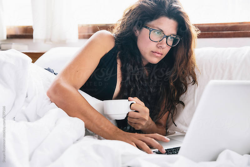 woman working in bed on a laptop with a computer by Shaun Robinson for Stocksy United