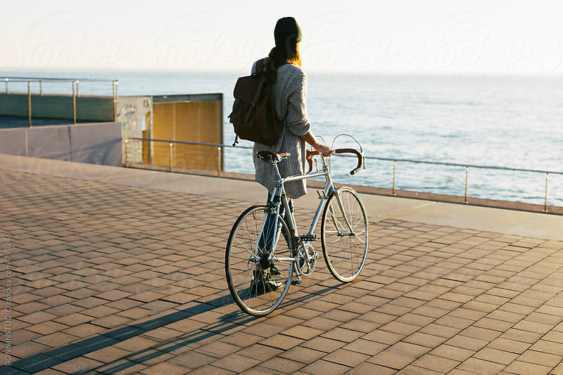 Back view of a woman walking with her vintage bicycle by the sea. by BONNINSTUDIO for Stocksy United