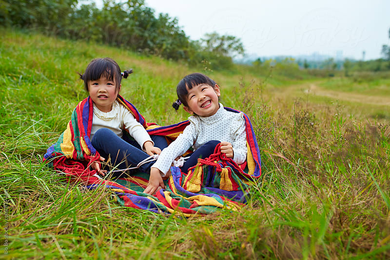 two lovely little asian girl having fun outdoor by Bo Bo for Stocksy United