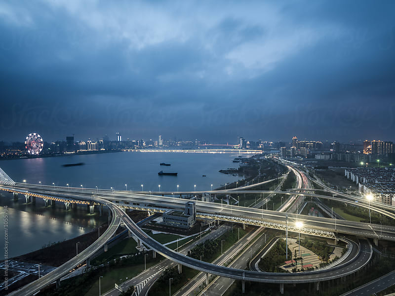 urban traffic road with skyline background at night by yuanyuan xie for Stocksy United