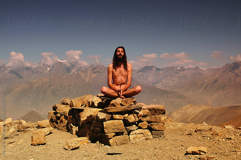naked wild man meditating in mountains by Alexander Grabchilev for Stocksy United