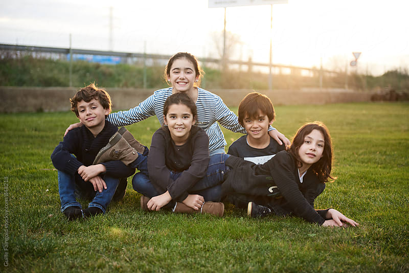 Five children on lawn smiling at camera by Guille Faingold for Stocksy United