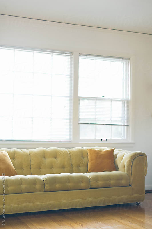 Vintage Yellow Couch in front of Windows in a Living Room by Briana Morrison for Stocksy United