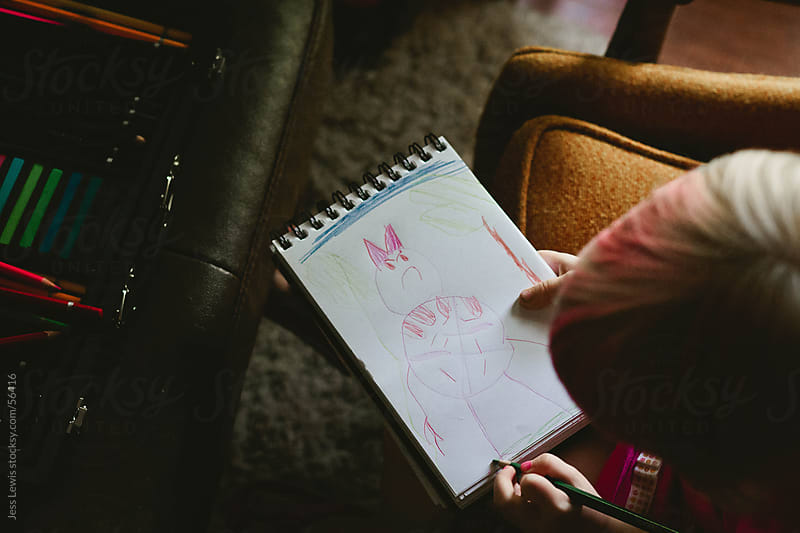 young girl drawing picture in a notebook by Jess Lewis for Stocksy United