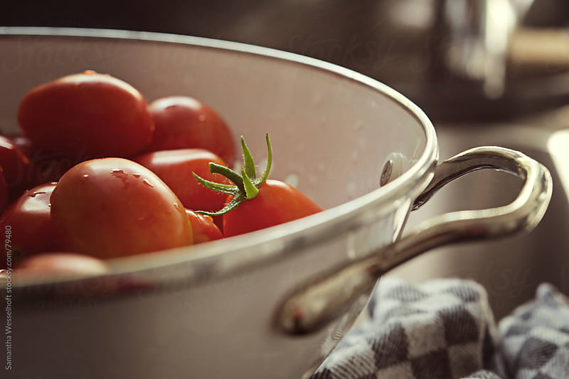 cherry tomatoes in a colander by Samantha Wesselhoft for Stocksy United