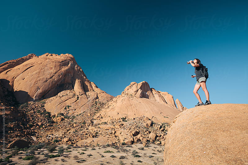 Female hiker drinking water in the mountains by Micky Wiswedel for Stocksy United
