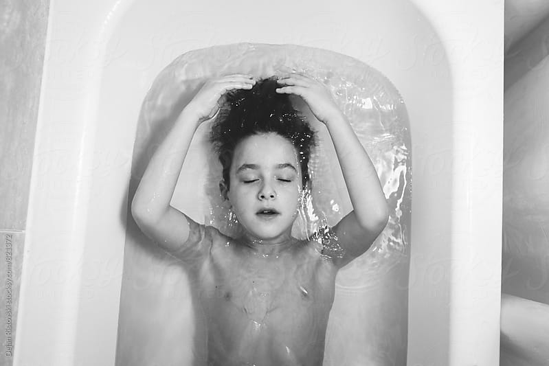 Boy lying in tub. by Dejan Ristovski for Stocksy United