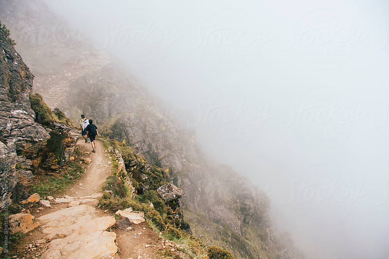 young trekkers walking along a path in the himalaya. by Shikhar Bhattarai for Stocksy United