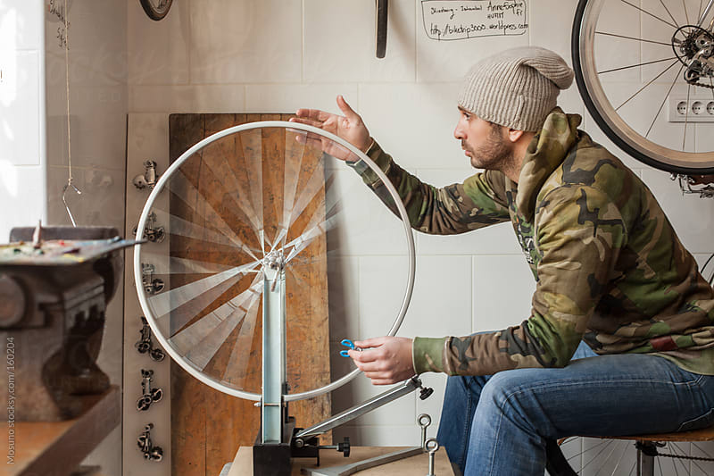 Man Working on a Bicycle Wheel by Mosuno for Stocksy United