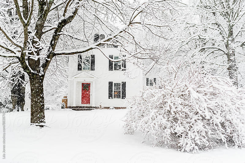 historic house in the snow. red door. by Léa Jones for Stocksy United