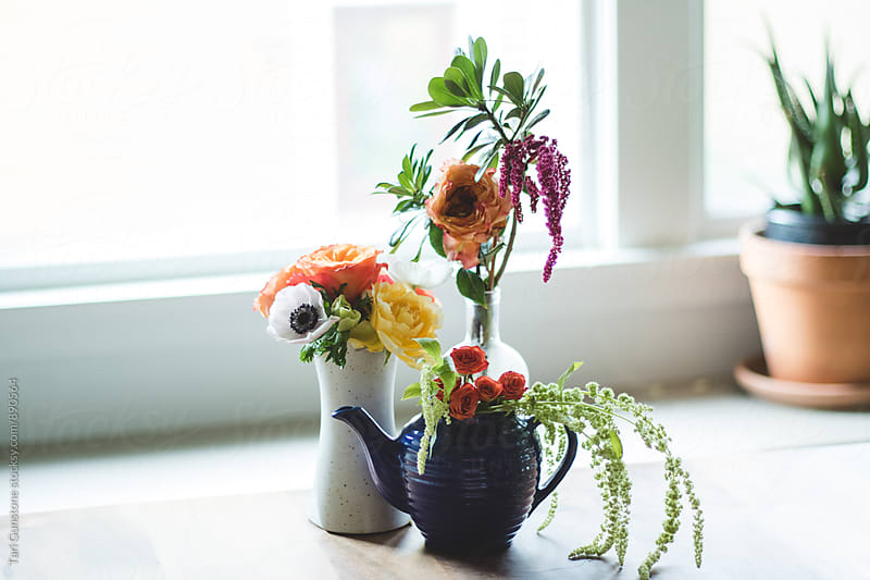 Still-life of colorful flowers in vases by Tari Gunstone for Stocksy United