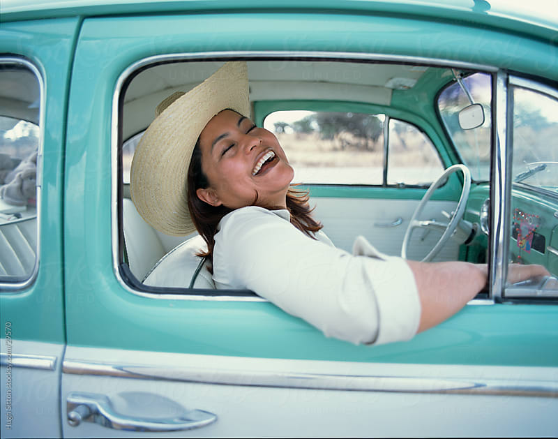 Happy, laughing Mexican woman sitting in her car. by Hugh Sitton for Stocksy United