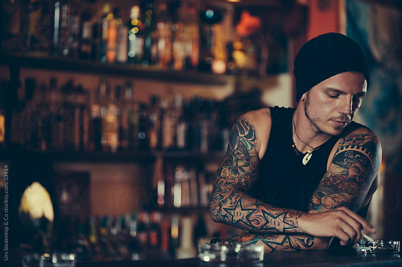 Bartender with mexican tattoo smoking by Urs Siedentop & Co for Stocksy United