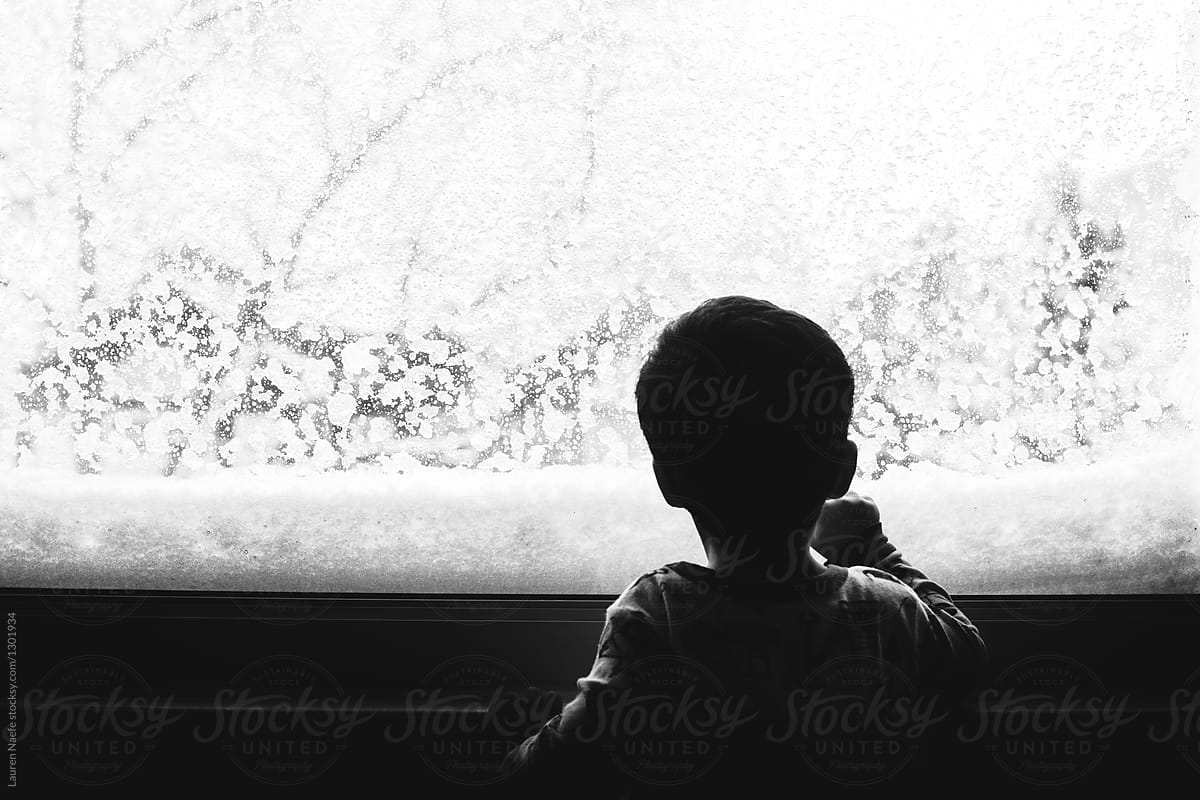 Little Kid Looking Out The Window On A Snowy Day By Lauren Lee Stocksy United
