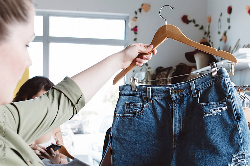 Young woman shopping for denim shorts in cute retail shop by Carey Shaw for Stocksy United