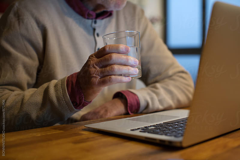 Closeup of an elderly man holding a glass of water in the late afternoon. by BONNINSTUDIO for Stocksy United