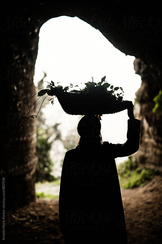 Woman in underground tunnel hold basket of foliage on head  by Kristen Marie Parker for Stocksy United